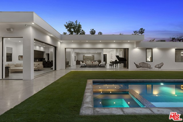 This stunning, private, and sophisticated single-story contemporary in the heart of Trousdale Estates boasts warm, rich interiors, walls of glass, high ceilings, and elegant floor plan. Grand entry invites you to open and comfortable living space, complete with fireplace, easy outdoor access, and automatic sliding doors. Chef's kitchen features high end appliances and separate butler's pantry. Sumptuous and spacious master suite is complete with inviting fireplace, lounge area, luxurious walk-in closet, and direct access to yard and pool. Secondary living room sits among the guest bedrooms, all of which have en-suite bathrooms. Backyard is exceedingly private, featuring grassy pad, pristine, pool, and bar. Located in close proximity to Beverly Hills shops and restaurants.