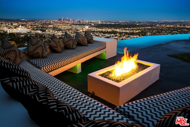 Gated and ultra-private warm contemporary with one of the most explosive and unobstructed views of downtown LA and beyond. Moments from the SunsetStrip, this property features floor to ceiling walls of Fleetwood pocket glass doors opening to an extensive backyard, featuring a 65' stunning infinity pool that spills into thesexy downtown views. A firepit lounge, outdoor bar, outdoor kitchen and a barbecue kitchen creating the perfect outdoor scene with yard; covered outdoor living, diningareas and an entertainment deck . A bright open floorplan with a fabulous custom chef's kitchen, Italian Cabinetry and top-of-the-line appliances open to the family roomand endless city views. Fantastic living and dining rooms, lavish master suite with office and stunning views with large deck and store size designer closet room. Finishedwith the finest materials. No expenses spared while creating an owner's dream home. Motor court for 9 cars plus 3-car garage.