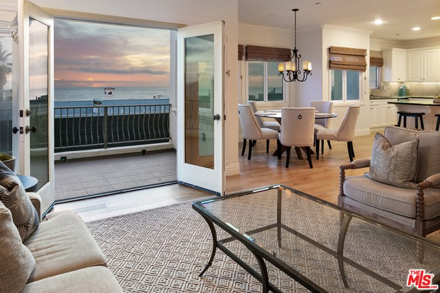 Panoramic, ocean views and open floor plan featuring balcony, kitchen & dining area from living room, at dusk (rd floor).