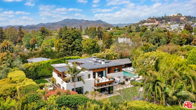 Situated on one of Pacific Palisades premier streets, this ultra-private, contemporary retreat showcases masterful craftsmanship and exceptional amenities. Surrounded by lush landscaping, the Zen-inspired, .68-acre estate is among the most spacious homesites in Upper Riviera. Envisioned by Grant Kirkpatrick of KAA Design, the 13,508-sq-ft residence boasts an open-plan living and entertaining spaces, artful details and a central atrium with 35 mahogany ceilings. Bathed in natural light, living, dining and family rooms leadto the magnificent chefs kitchen and expansive resort-style backyard with a pool, spa, waterfall, koi pond and Lanai with alfresco dining and lounging terraces. Amenities include a game room, bar, office, gym, media room, staff quarters and wine room. 7 bedroomsinclude the stunning primary suite with dual dressing rooms and spa-style bath. Offering absolute privacy and serenity, the home is located moments from The Palisades Village and The Riviera Country Club.