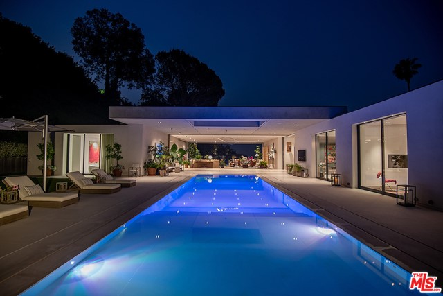 PROPERTY OFFERED FURNISHED W/SOME EXCLUSIONS (art & accessories excluded). Warm Modern Masterpiece set on an over 31,000 sq.ft. lot in prime lower Trousdale Estates w/beautiful city views. Newly built in 2016, this property offers epic scale w/high ceilings, open spaces & walls of glass that disappear & blur the lines between the indoor & outdoor spaces. Situated behind private & discrete gates leading to the large mtrcrt & impressive floating entrance w/water features & pivot front door. Enter into the voluminous main gallery connecting the various public rooms. Designed for large scale entertaining, the vast living rm flows to the outdoor living rm & zero edge infinity pool. Formal dining rm, state-of-the-art kitchen, secondary catering kitchen & family rm w/glass enclosed temperate-controlled wine display. The master suite features beautiful city views, incredible walk-in closets & spectacular bath. 4 add'l bdrm suites each w/walls of glass opening to the grounds & staff quarters.