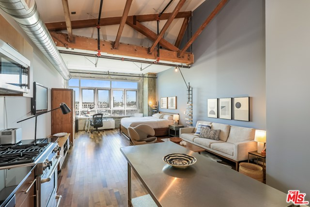 Stunning TOP FLOOR loft in the heart of the Arts District.  Beautiful high ceilings with exposed timbers lead your eye out to the view of snowcapped San Gabriel Mountains.  The loft features huge windows, custom shades, hardwood floors, bathroom with private laundry closet, and a modern kitchen.  The HOA recently completed a beautiful renovation of the rooftop pool and activity deck, offering spectacular views of the downtown Los Angeles skyline.  Plenty of private cabanas grills, and a hot tub complete the outside portion, while you can enjoy the same view from the rooftop gym.  The building has 24 hour security and card access.  Parking is a breeze, with your space on the top floor of the attached parking deck as well.