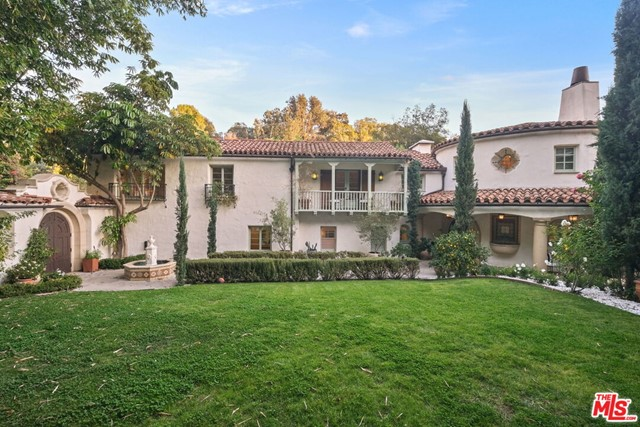 This Spanish Revival estate, known as Casa de Seis Palmas, has a storied Hollywood past and offers utmost seclusion and privacy behind lush landscaping. This luxurious celebrity hideaway has been home to actress Marion Davis, record mogul Ahmet Ertegun, and supermodel Tyra Banks. The home boasts an abundance of light and beautiful details like travertine stone and wood-planked floors throughout. The spacious living room is framed by a majestic vaulted wood-beamed ceiling, French doors, and grand floor-to-ceiling windows. A chef's kitchen comes replete with custom cabinetry, large center island, and top-of-the-line stainless steel appliances. The grand owner's suite features a sitting room, enchanting city and ocean views, and walk-in closets with gorgeous Spanish tile. An entertainer's paradise, the patio opens to a full outdoor kitchen, casita, fire pit, and pool. A library, sunroom, formal dining room, guest suite/media room with private entrance and full bath complete this one-of-a-kind home.
