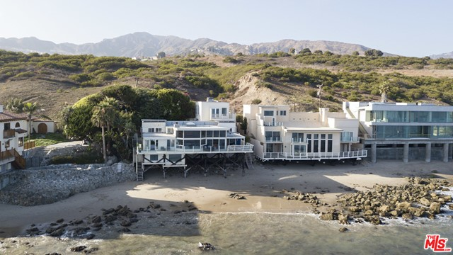 A rare oceanfront opportunity on Malibu Road with approx. 75' of beach frontage, pool and spa and a separate guest house!  Enter this charming 4 bedroom, 4 bathroom property through a private gated entry into a walled courtyard surrounded by overhanging trees with pool and ocean view spa, built-in BBQ, wonderful entertaining areas and stairs to beach. Enjoy stunning ocean views from the spacious living/dining areas with high ceilings, floor-to-ceiling windows, a fireplace, kitchen and wrap around ocean view deck perfect for entertaining and oceanfront dining. The master suite is oceanside and opens to the deck. The other two bedrooms offer ensuite bathrooms, one has double doors leading to the pool, the other has a fireplace and access to an ocean view deck. There is a fabulous separate guest house above the garage with one bedroom, one bath, kitchen, ocean view deck and private entrance. Includes plans and permits in process for remodel.