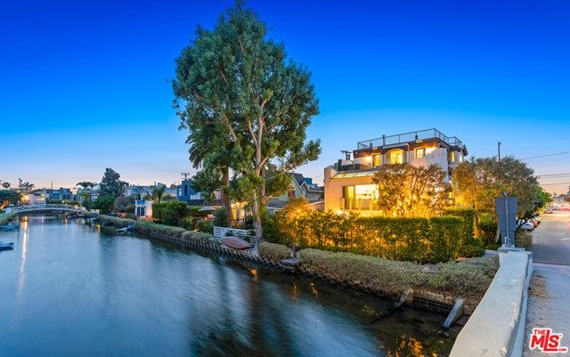 Breathe in the ocean air in this incredibly rare find located in the Venice Canal. This 5 bed / 3.5 bath contemporary home with parking for 6 cars sits on a corner lot with views from every floor and plenty of natural light that shines throughout. Enjoy the weather and entertain in style on the front patio with built-in BBQ, firepit and plenty of seating that flows into the large living room with a fantastic wet bar. The bottom floor also contains 2 guest beds and a bathroom. The main floor features an open concept living and dining room highlighted by high ceilings throughout and floor to ceiling French doors that peer out over the canal. Through the hallway you'll find two more large guest bedrooms and a large guest bath. The entire third floor boasts an expansive master suite that flows out onto a large balcony with breathtaking views that you can soak in as you relax in the hot tub. The master suite is rounded out by a stunning spa-like bath and plenty of closet space. Relax underneath the stars on the massive rooftop deck with 360-degree views. Whether you want to entertain or relax in style, this home offers a once in a life opportunity to enjoy all the best that Venice has to offer.