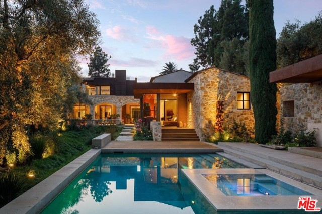 Enter pvt gates, under a hedge arch & into a refuge of nature. Luis Ortega & Jose Fernandez, collaborated on this Beverly Hills 3bd/3ba, 2powder Tuscan Villa. The exterior harmonizes w/ the limestones earth tones, rustic wood beams & striking CorTen steel enveloping the timeless home. Enter a glass foyer into a symphony of refined simplicity, clean lines & a luxurious palate of stone, wood, steel & glass. Stone floors lead to a FLR w/ fp. The chefs kitchen & dining rm captivates w/ a bold stone frame, stainless-steel countertops & adjacent breakfast rm. The billiard rm is adorned w/ a venetian plaster ceiling. The master suite offers a lib/office, venetian plaster walls, vaulted ceiling w/ steel frame panel, floor-to-ceiling windows & 2 luxurious bath suites. 2addtl bdrms complete the floor. The outdoor space flaunts impeccable landscaping, pool, spa & pool house. Addtl amenities: greenhouse, 2-car carport & a loft w/ office, gym, art studio & observation deck. A truly idyllic estate.