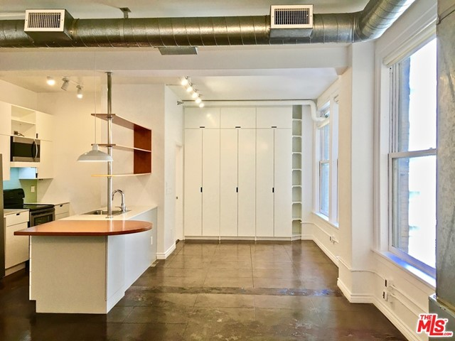 This 6th floor open loft in the historic Bartlett Building is available immediately. Nicely upgraded features include a remodeled kitchen and bathroom, abundant and bright overhead lighting, built-in floor-to-ceiling closets, and an in-unit washer/dryer. This apartment faces East towards the interior courtyard and has views of Spring St. via the alley. Also enjoy beautifully polished concrete floors throughout and large original windows for lots of light. Full kitchen appliances include a microwave, dishwasher, electric stove/oven, garbage disposal, and refrigerator. Be in the heart of the Downtown LA Historic Core where you're in close proximity to shopping, dining, nightlife, and public transportation. The building has a lovely roof top lounge area fully furnished and perfect for outdoor dining with 360-degree views of the Downtown skyline, and a 24/7 concierge for security and convenience.  Parking included for one car in the private garage. Space #15, lower level.