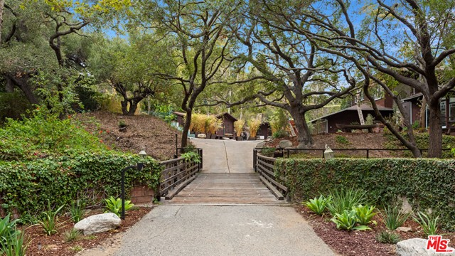 This magical, roughly 1-3/4 acre property is located on Evans Road  a private, country lane bounded on one side by Will Rogers Historic Park (and its famous polo field) and Rustic Canyon Creek (a year-round waterway with natural waterfalls which runs to the Pacific Ocean) on the other. The meandering one-half mile lane, dotted with bridges criss-crossing the creek to the 16 homes located on it, has long been a little-known community, home to globally-known politicians, actors, and industry leaders. Zoned for horses, it's common to see one trotting down the lane and up the trail to the Park and the miles of equestrian and hiking trails beyond. An abundance of towering Sycamores, Eucalyptus and Oak trees conveys a park-like quality and ensures the ultimate in privacy. Maintain the charming remodeled 4,100+ SF, 5-bedroom home, complete with pool and N/S facing tennis court, or design the estate compound of your dreams. Crest Real Estate Report and preliminary programming and design by world-renowned architects Woods + Dangaran are available.