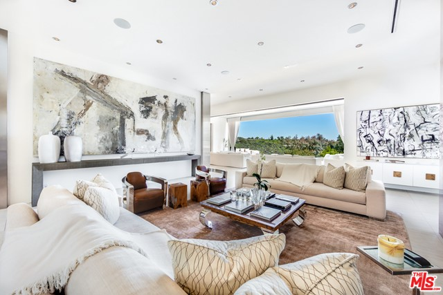 Glamorous contemporary living in prime Bel Air. A true timeless masterpiece featuring the latest in technology, materials and infused with Old World class and spectacular magic. Completely remodeled and completed in 2014. A state-of-the-art open floor plan, grand open kitchen/family room and breakfast nook seating for 10. A master wing with extensive private outdoor covered patio, fireplace, infinite his and her master baths and closets designed for today's royalty. This home also features, a vacuum elevator, theater, office, 23' grand foyer ceilings and high ceilings throughout. 3 exquisite staircases, 70' quartz infinity pool spilling into a picture perfect view, remote controlled disappearing walls of glass seamlessly joining the outdoor living rooms and patios with the decadent grand rooms inside. Gated circular motor-court for 10 cars with oversized 3-car garage. Extremely private with endless and breathtaking mountaintop views.