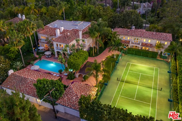 A rare opportunity to acquire two side-by-side lots in the Beverly Hills Flats. This compound encompasses nearly an acre of flat land offering total privacy with one main house, a separate guest house, pool house, and garage parking for 9 cars. Manicured grounds feature a big pool with spa and cascading water feature, pool side misting system, full-size tennis court, huge outdoor kitchen, and dining pavilion for resort-style living. The grand 9,288 sq ft main house boasts a soaring sky-lit entry, formal living and dining, huge eat-in kitchen and breakfast area, family room, office/study,  the primary suite with dual ensuite bathrooms, 4 additional ensuite bedrooms and service quarters. Overlooking the tennis court is the guest house with 5 ensuite bedrooms, powder room, high ceilings,  and elegant contemporary finishes -- a style that carries over to the pool house that's nestled in the beautiful manicured mature landscaping. An exceptionally rare find, this meticulously maintained property is the ultimate Beverly Hills Estate.