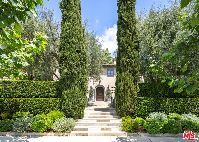 Stunning, published 1927 French Mediterranean. Former home of renowned architect William Hefner and his designer wife Kazuko Hoshino.  Entry courtyard with olive tree and fountain to a classic 2-story main residence reminiscent of the French countryside with high quality finishes and materials throughout.  Limestone window and door sills, refinished wood and restored period details. Beautiful living room with fireplace opens to terrace and gardens. Formal dining room, library/office, chef's kitchen featured on HGTV with Calcutta gold marble, solid oak cabinetry, oversize center island, elevated fireplace and breakfast area opening to expansive terrace.  The master suite has high ceilings, gorgeous marble bath, large walk in closet, fireplace and opens to view terraces on both sides.  A separate large 2 story pool house/guest house/gym with 2 baths, inviting 2nd floor terrace with built in seating and fireplace.  The incredible grounds include a 50 foot lap pool, sculpted hedges and incredible mature sycamore tree.  Don't miss this incredible opportunity!
