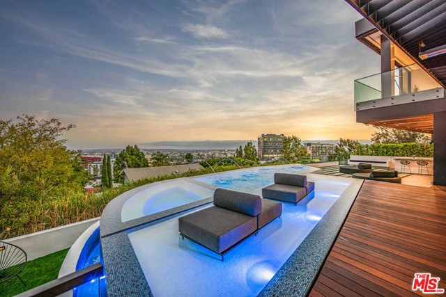 Perched atop the Sunset Strip, this warm, contemporary residence, designed by world-renowned architect Hagy Belzberg offers the amenities and experience of a luxury resort - a true tranquil paradise of architectural significance. Featuring one of the first digital NFT art home installations and equipped with a temperature-controlled glass wine cellar, dual kitchens, 2 outdoor bars, Crestron home automation, Sonos sound, 4-sided infinity edge pool and fire pit overlooking panoramic views. Other notable details include motorized sliding glass walls, striking runway-style driveway 30-feet above the street, motor court with turntable, air-conditioned 3-car garage, along with a 24-foot glass water feature that cascades down all 3 floors. The lower level is a sultry and polished private speakeasy with dark leather and walnut-paneled walls, movie theater and stunning bar area. The 4 ensuite bedrooms upstairs are punctuated with amazing views from DTLA to the ocean. Enjoy proximity to fine dining and shopping.