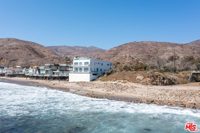 RARE MALIBU COMPOUND ON THE BEACH WITH 180 FRONTAGE AND GRAND RESIDENCE!  Unique opportunity on world famous County Line surfing beach for a gorgeous, 2020 renovated estate w/adjoining lot on approx. 1.3 acres totaling 180ft of accessible beach frontage on a low bluff. Main residence spans 5049SF w/approx. 2000SF of usable roof deck (one of the largest in Malibu) and has unobstructed ocean, island, & mountain views. Sprawling decks to watch surfers, wild life, & the best sunsets from Catalina to Channel Islands. Captivating first level features a 30x50 living room w/oversized ocean view windows, deck, & fireplace. Be led to the formal dining room where you can continue to relish the vistas. Chef's kitchen w/Viking & SubZero appliances, ample cabinets, & island. Spacious master suite w/windows & private deck highlighting the ocean views, den, & spa-like bath. There are 3 add'l family beds, plus in-law suite w/fireplace, separate entry, kitchen, & deck. Roof deck w/BBQ and lounge/dining spaces all enveloped by incomparable 360-degree ocean to mountain views. Set at the point of County Line, the private, white sand beach is famous for the most consistent surf. Use the adjoining large, flat lot for 2nd residence, guest house, pool, tennis courts, & more. An incredible value & rare investment opportunity for 2 large parcels on the beach!
