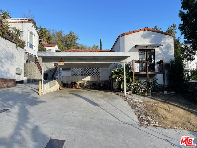 On Sunset Strip. Sitting above the Viper Room, Roxy, and other major attractions.         It is a charming House and 3 additional units of residential property that could be legally rented.   The house was subdivided thus, there are 5 units as of now, but it can be easily re-united back to a single house.  The location is perfect - it seats on the hill  North of Sunset, but the lot is flat and buildable. Easy access from Sunset.