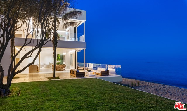 Luxurious architectural on two separate legal parcels on private road with 130 feet of beach frontage and one-of-a-kind coastline/island/ocean views. Sleek design by Chad Oppenheim for indoor-outdoor living and entertaining features Venetian plaster, rift sawn white oak, huge vanishing pocket doors, Navona travertine floors. Gated, very private, three levels with elevator and gorgeous spiral staircase. Landscaped courtyard entrance. Open main floor living/dining/kitchen with high ceilings, wraparound glass walls that open seamlessly to oceanfront deck and patio. Living area has fireplace, gallery walls, two large seating areas, one open to ocean, the other open to an outdoor garden living room with fireplace and fountain. Beachfront deck has additional seating and ample room for entertaining and al fresco dining. Two kitchens include long island, bar seating, beautiful oak cabinets, top-grade appliances. Upper floor has large indoor/outdoor living room with glass ceiling and wood beams, plus four en-suite ocean-view bedrooms including two owners' suites. Bottom floor has temperature-controlled wine storage, media room, laundry room. Room for a guesthouse (under construction) 2nd residence, & oceanfront pool next to an expansive lawn and 100-year-old Olive Grove. Two-car garage, guest parking for 14 cars, beautiful landscaping, many smart-home features.