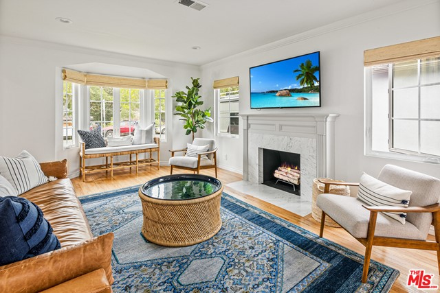 Live the Santa Monica dream with this beautiful turnkey, light and bright home with an incredible yard nestled in coveted Sunset Park. The sellers kept the original charm and remodeled the rest! The exterior has been refreshed with new white siding and stylish black windows which let in tons of natural light and are accompanied with custom window treatments. The extensively remodeled chef's kitchen features stainless steel Frigidaire Professional appliances, a farmhouse sink, white shaker cabinets, and floating shelves. The bathroom has been renovated with a classic design that includes a double vanity with a concrete countertop and Spanish tiles. Other highlights include beautiful, original hardwood floors that have been refinished throughout the home, original crown molding, built-ins, and the original fireplace has been redesigned with white Carrera marble surround. The two spacious bedrooms are steeped in sunshine and a formal laundry room with a butcher block countertop is also included. The detached two car garage is the perfect flex space for a home gym or office, and includes plans for a full ADU conversion. The massive yard has been beautifully landscaped and features orange and lemon trees. Highly desirable location close to Grant Elementary School and just a stone's throw away from shops, restaurants, and parks.