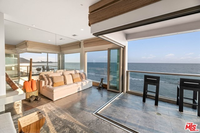 Meticulous in every detail, this gorgeous & sophisticated Carbon Beach home is part of a 4-Unit building & walking distance to Nobu, Soho House & the iconic Malibu Pier.  No expense was spared on a recent remodel including multi-fold doors which seamlessly open the living area to the deck and the stunning ocean & Queen's necklace views.  A custom, gourmet Poggenpohl kitchen overlooks the dining area, living room and ocean view beyond.  The Owners' suite has heated floors, a fireplace, cedar closet, balcony and a bath with a Zen-like feel including bamboo sinks, tile floors and an in-mirror TV as well as another huge walk-in closet. The second bedroom is also en-suite with an equally beautiful bathroom. In home laundry area, private two car garage w/additional deeded guest space, rooftop deck...everything you need for a beach getaway or a full time residence. Full exterior remodel of the common spaces just completed as well. This home is truly a work of art.