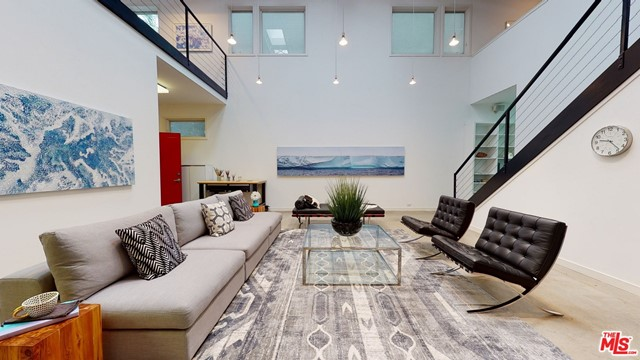 Nestled in the celebrity community of Venice this elegant Architectural New York style loft masterpiece is perched on one of the best locations in Venice with incomparable workmanship and design. This beautiful open floor plan light-filled architectural home offers over 4600 sq/ft of living and entertainment space with 4 bedrms and 3 full baths with very high ceilings & great wall space for artwork.  A two-story formal entry leads to a gorgeous living room with polished concrete floors.  To the left, incredible four-car garage has 2x height ceilings, concrete flooring, custom storage & a roll-up gate. Three bedrms downstairs with one impressive en-suite master bedroom w/den. Another bedroom offers a recording studio within the bedroom and a third bedroom has an open floor space which includes a large office space.  All bathrooms have an inviting walk-in shower, and the upper-level shower has room for a spa tub.  Walk to the upper floor, to the left en-suite master bedroom with open walls & an enormous walk-in closet w/custom shelving.  A Lovely roof-top deck to enjoy the sun during the day or wine gathering at night overlooking treetops. To the right of the stairs, Designer kitchen boasts Cesar stone counter-top with Berlin customized commercial range hood and High-End appliances.   Upper level also features a very large living and dining rm.