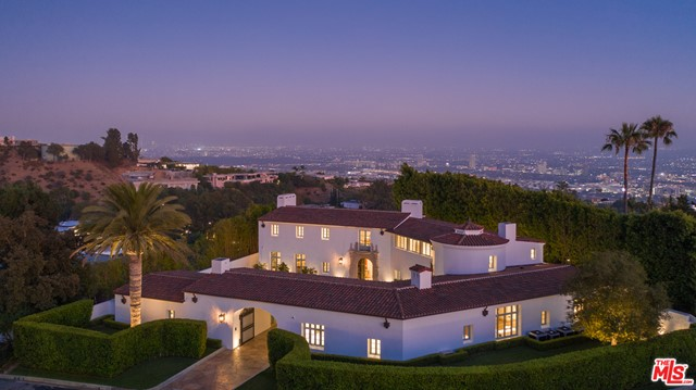 """Now listed at $10M below the initial market price! Newly built and never occupied, this uniquely realized world class estate is on a quiet cul-de-sac in one of Los Angeles' most coveted neighborhoods with neighboring homes selling upwards of $40 million. Designed by award-winning architect Richardson Robertson III, renowned for """"Fleur de Lys"""" in Bel Air, the home boasts striking views from downtown to the ocean, with meticulously designed interiors and finished with the finest European materials. Features include four bedrooms, eight baths, 800-bottle wine cellar, theater, library and a """"to be completed by the builder"""" entirely redesigned & enlarged rear yard and sparkling pool with skyline city views. The lavish master suite features fireplaces in the bedroom and sitting room capturing sparkling, top-of-the-world views. Unique to the area, a Porte cochere leads to lush, level gardens circling the grounds. A perfect combination of International luxury and glamorous Hollywood lifestyle."""