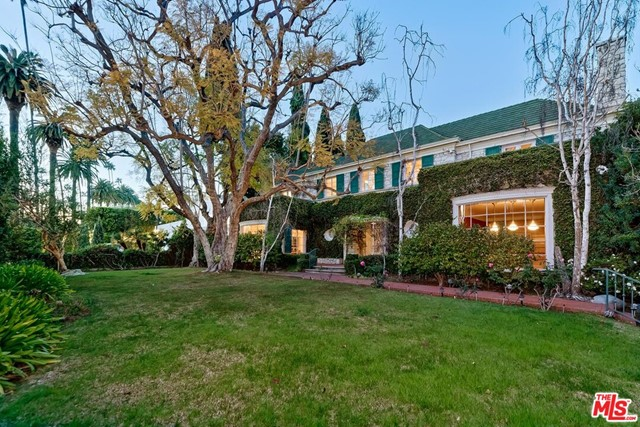 First broker previews by appointment only between 11-2 on Tuesday, April 13th. Please RSVP only via email to book a time. Trust Sale. 1st time available in 46 years. Sited on a lushly foliated corner lot of nearly 29,000 sq ft and over 300 feet deep, here is a once-in-a-generation opportunity to acquire and restore this glorious, grand, and classic 2sty Traditional estate by world-renowned Paul R. Williams, FAIA. The expected attention to detail is apparent throughout with extraordinary mouldings, wood floors, curvature, and French doors. Voluminous scale exhibited by a baronial-sized dining room, massive reception foyer with sweeping staircase, huge kitchen/great room, and a tremendous family room with bar. Kitchen/vaulted-ceiling great room and family room, and a striking oval breakfast room open to fabulous deep grounds with lawns, pond, pool, two separate guest units, office, pool baths. 4 magnificent bedroom suites upstairs along with a lounge area and laundry closet. Maid's quarters downstairs. Secondary laundry room near the guest units. Large basement area for extensive storage capabilities. A supreme address centrally located in the Flats of Beverly Hills along with a significant architectural pedigree makes this a property to cherish for many years to come.