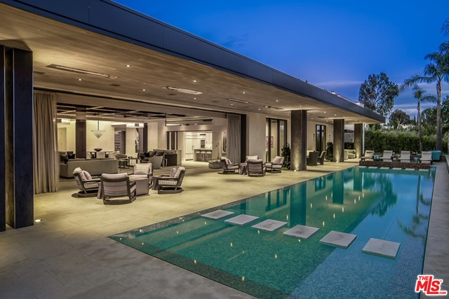 Over $42mm invested. Priced $10mm under comps. The best buy in Beverly Hills. Over 13,000 square feet on over an acre in lower Trousdale, featuring a sprawling entry hall leading to a great room with a motorized wall of glass overlooking the outdoor spaces, infinity edge pool, and city lights. An elegant gallery leads to the master suite which offers dual baths, shower garden, massive closets, and fireplace. 5 additional bedroom suites, one of which is a hotel style suite with a separate sitting room and dual closets. Other rooms include a professional THX 3 tiered screening room and indoor and outdoor catering kitchens.  The home was designed to showcase art with museum style tracks and lighting. Spectacular grounds with one of the largest flat lawns in Trousdale. With all of this comes approved plans for a 3600 square foot two story guest house the only of its kind permitted in Trousdale. Complete privacy behind gates and a security guard house. A Trousdale Showplace!