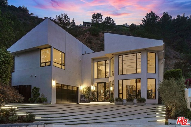 Impeccably designed by award-winning architect Michele Saee, this ultra-contemporary smart home rests upon a rare 2.27-acre parcel of land at the top of a cul-de-sac in Pacific Palisades with expansive hillside and city views. Showcasing functional living spaces and a fresh art gallery-style design, the home is replete with light porcelain floors and walls of energy-efficient windows that fill each space with incredible natural light. Through the foyer, the great room instantly captivates with two-story ceilings, flowing seamlessly into a flex living space and dining area with a 2,200-bottle wine cellar. Also on the main level is the gourmet kitchen, complete with custom Italian lacquered cabinetry, Gaggeneau appliances and a 16' island with quartz counters. The home features four en suite bedrooms, including the luxe primary suite with 20' closet, resort-like bath with Toto Neorest and tranquil balcony, and comes fully equipped with a Crestron system, solar panels, backup 22 kW Generac generator, elevator, and 2-car garage with epoxy floor. Just outside lies a lush hillside oasis with a built-in BBQ, lounge areas, fruit trees, vegetable garden, firepit, and pool and spa for ultimate relaxation and entertainment. Contemporary in design yet comfortable by nature, this home sets an entirely new benchmark for future-thinking design in Pacific Palisades.