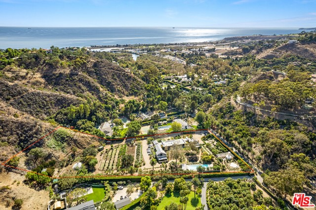 This unique 7 acre estate is situated in the prestigious gated private community, Serra Retreat, and is comprised of two separate parcels with a newly constructed contemporary home. This stunning 11,358 sf home has 6 bedrooms, 9 bathrooms, a private pool with an adjacent cabana, bathroom, shower and steam room. There are two large two-story primary suites with second-story outside decks, a spacious closet, marble master bath with Bulthaup vanity, and Dornbracht plumbing fixtures. The primary suites are on opposite wings of the house. There are 4 additional bedrooms, 3 on the first floor, and a large guest suite in the basement. There is a large open floor plan with an expansive living/dining room, as well as an open floor plan kitchen/family room with breakfast nook. The first-floor public spaces flow into a large exterior patio with the interior doors in both spaces fully opening to the patio. The basement has a large light well with a botanical installation. There is a large sunny multi-purpose media room and a great laundry room with double washer/dryer. The home has a CCOF Organic Farm, featuring honey bees, goats, and chickens. There are two wells on the property with a 5,000-gallon tank reverse osmosis water treatment system for the well water, which allows for unlimited access to clean water for property-wide use. The property also has 2 yurts, 16ft and 30ft, and a farm restroom with a shower. This green, sustainable, clean living home is picturesque day-and-night, all year-round and is an incomparable combination of country side and modern living.