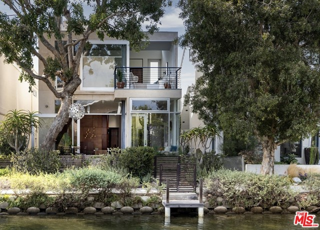 This published architectural home, designed by Glen Irani situated in coveted Canals of Venice is a peaceful retreat filled w/ luxury comforts & creative, modern design. 3 level residence, 3 bed/ 3 bath offers a spacious, open floor plan, walls of sliding glass doors, custom walnut cabinetry & brass hardware & rooftop garden. An abundance of light, beautiful views of the canal & sea breezes fills this home! A spectacular open chefs kitchen w/ state-of-the-art appliances & expansive double height living space w/ curvilinear walls & an architectural fp. 1st floor opens to a garden & patio w/ fire pit & bbq perfect for entertaining. Guest suite, cozy den, & 2 car garage w/ ample storage complete the ground floor. 2nd floor, there is a grand screening room or office, guest suite, & primary suite feat walk-in closet, large bath, & outdoor balcony. 3rd floor rooftop deck, stocked w/ hot tub, outdoor shower, & steel & glass solarium room. This gem of a home, filled w/ built-in architectural features, luxury comforts, & plush outdoor spaces, creates a relaxing oasis secluded from the world outside. A rare home, perfect for entertaining friends to retreating into ones own private compound. Situated close to the beach and nearby Venice shopping & eateries, this is Venice living at its best!