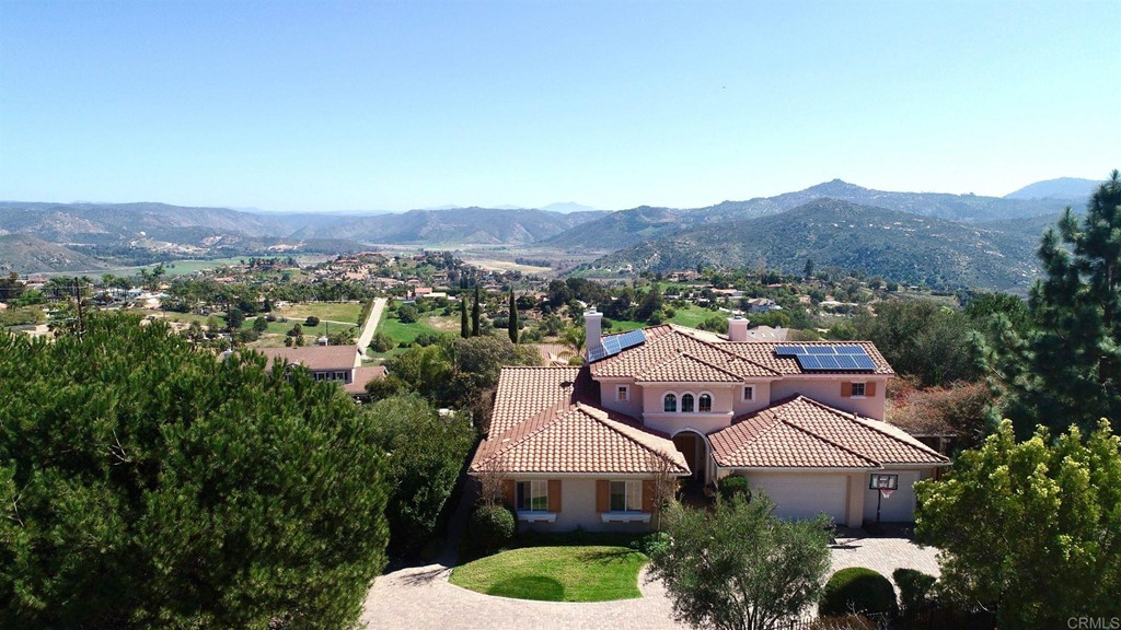 Panoramic views of the San Pasqual Valley & Safari park from this lush one acre completely fenced and automatic gated estate. Additionally, this single level mediterranean home features an office with built in cherry cabinetry with a fire proof safe and a HUGE loft / bonus room. Other notable features include an entertainers kitchen featuring a Viking 6 burner cooktop, Sub-zero refrigerator, Bosch dishwasher, separate spice drawer, glass front cabinets for display, dual ovens, walk in pantry, all surrounded by gorgeous walnut cabinetry. The spacious living areas capture the fabulous unobstructed views from 22ft. ceilings inside and breathtaking views from the patio, BBQ/outdoor kitchen, infinity edge pool, orchard, garden area and the lawn area with walking path. This home was designed to provide outstanding indoor/outdoor California style living.  An outdoor entertainers dream  as you walk out of the patio doors which include disappearing screens opening up to the outdoor living area featuring a Viking BBQ, outdoor kitchen, disappearing edge pool with cover and an aluminum pergola providing a shady area for morining coffee, afternoon tea or evening wine. Murals painted by noted artist Robin Golden! the true Tuscan touch! The lushly landscaped property also features a plethora of fruit trees: fig, apple, pear, lemon, lime, guava,grapefruit, plum, apricot, orange, avocado, pomegranate and grape vines. There are raised garden boxes for the veggies and a rose garden. The equally important features that give this property it's added value include a 24 zone irrigation system controlled by app on your phone, 3 level LED lights on the roof perimeter that light up at night, an app controlled security system with direct connection to fire and police, whole house water purification system, 45 solar panels leased from Sun Run and whole house wired for sound inside and out, cable and satelite.  Fantastic value in the details of this well planned home!