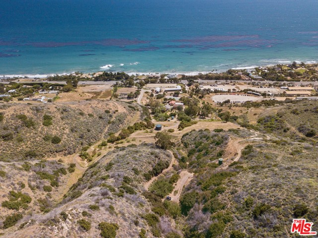 RARE 25- acre Malibu compound & unique opportunity for developers, horse-enthusiast & more! A truly one-of-a-kind opportunity to own an estate w/awe-inspiring ocean views, remarkable features & potential! Exquisite equestrian facilities w/9 state-of-the art stables w/Crestron cameras, showers for horses, tack room & lounge w/ocean views, full bath & changing area. Computerized arena w/turf-water springs (from Austria) to ensure optimal riding. Beautiful house steps from stables w/garage, laundry room, living flows to kitchen/dining, bath & picture windows welcoming floods of light. Unique water filtering/storing system thru 4 veins in canyon resulting in thousands of gallons to service property. 75,000 gallons are stored on the property in 4 tanks on a regular basis. Includes 15 acres of buildable land, flat area designated for helipad, horse trails, outage generator, main house w/ocean views, recently renovated guest cabin w/koi pond, tennis court, 2 gated entrances off PCH & more.