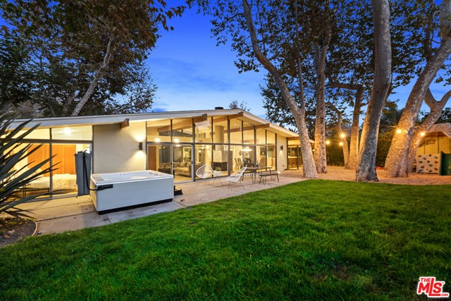 """Also available for annual lease at $12,000 per month. Beautifully remodeled mid-century, """"atrium-style"""" home, one of the most desirable residences in Malibu West with courtyard entry, floor to ceiling walls of glass, abundant natural light, gourmet kitchen, 3 luxurious baths, 4 bedrooms, all new flooring, new AC, new master bathroom and walk-in closet, whole house water filtration system, new oven and dishwasher, new LED lighting throughout.  Spacious backyard next to seasonal stream, majestic sycamore trees, featuring an outdoor spa, and cement patio/decking areas. Crisp, clean and turnkey w/ all the amenities of Malibu West including private beach club and tennis court privileges."""
