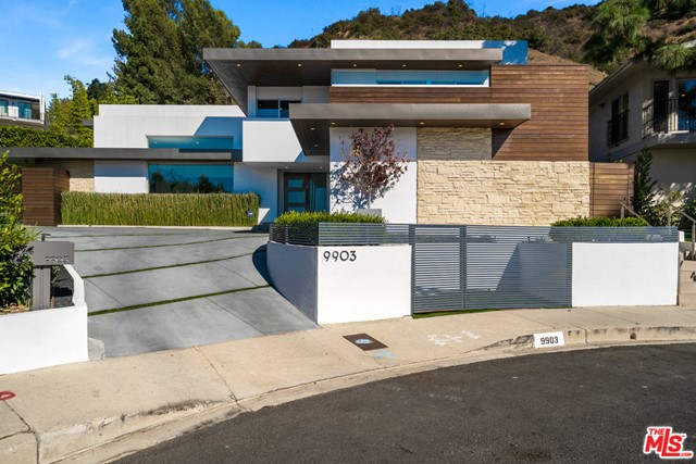 Fully remodeled this contemporary Beverly Hills home is an incredible opportunity to own one of the most valuable properties in 90210. Located off Benedict Canyon at the tip of a cul-de-sac 9903 Anthony Place sits on two lots (9903 and 9901 Anthony Place) both available for sale. 9903 showcases a proper ensuite master bedroom featuring views and a spacious walk-in closet not only functional but beautiful possessing top of the line cabinetry, an accessory island and a glamorous sit down vanity. 9903 Anthony Place comfortably displays an open floor plan containing four bedrooms upstairs and a maid's quarters/office down. The gourmet kitchen praises distinctive Calacatta marble, bar seating and a peninsula styled counter providing overly sufficient room for prepping and cleaning. The family room swags a fireplace, a wet bar, wine room and walls of windows providing an abundance of natural light to a mesmerizing view of the back yard engulfing an in ground saltwater pool, spa & grass area.