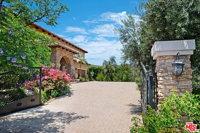 A beautiful Tuscan home on a 5.34 acre lot with views that embrace the mountains and ocean and is surrounded with landscaped gardens and covered patios. Soaring ceilings in the entry foyer, leading to generous sized living room, family room, dining and kitchen all opening out to patios. Built in Barbecue area, dipping pool and another patio with fireplace and TV.  5 bedrooms and a large upstairs bonus room with separate entry, make the 6,578 sq ft home only 10 minutes to the beach a very special home!