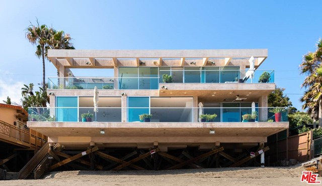 Thoughtfully redefined and completely rebuilt, this modern contemporary Malibu Beach home includes 76 feet of sandy beach frontage located on one of the most sought after sections of Malibu Road. Redesigned in 2000 by acclaimed Obermeyer Architecture, this custom rebuild features 180 degree ocean front views through floor to ceiling glass sliders from Palos Verdes to Point Dume. Bask in the ocean air on both levels expansive view decks whose sandstone flooring highlights the bright decor of this 6 bedroom / 6 bath home. As a single family residence or legal duplex income property, this home offers both buyers and investors the quintessential Malibu lifestyle.