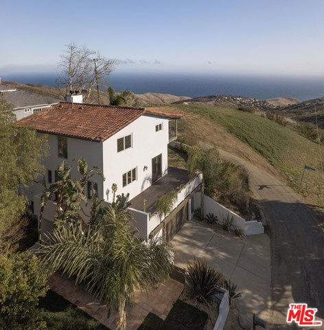 Stunning ocean views from this beautiful Spanish home set in the Malibu Mountains. The home is ideally set allowing both a flat grass front yard taking you up to the front door and an expansive grass backyard with wrap around deck taking full advantage of the corner lots views of both Mountain and Ocean views. The main level open floor plan allows for easy flow between the living, dining and kitchen, which is slightly tucked away allowing enough privacy while still being connected. The main level also has a bonus room that can easily be used for a 4th bedroom or an additional living space as it opens up into the living room. Upstairs includes 2 bedrooms with a Jack & Jill bathroom and the master suite with high pitched ceilings, beautiful ocean views from the bedroom & deck and bathroom with separate bathtub and shower. The property also features a nearly 1,300 sq. ft. garage underneath the home where you could easily have a 2 car garage and separate studio with windows looking out and doorway to front patio already in place. This charming Spanish home is a hidden gem in the Malibu Mountains and won't last long.
