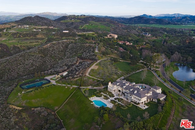 Redesigned and renovated by designer Roy Sklarin, this luxurious French Formal estate is beautifully situated on over 20 spectacular acres of land. The palatial residence features 14,000 square feet of lavish living space, 7 bedrooms, 13 bathrooms, comprised of a deluxe master bedroom suite with dual baths, walk-in closets, a gourmet double-island kitchen and pantry, a wine connoisseur's tasting room, a theater, a gym, a separate guest quarters. The property is being offered furnished with its custom-made furniture, chandeliers, hand-made rungs and draperies. The private paradise boastsbeautifully landscaped lawns, Magnolia-lined limestone walkways, hand-carved fountains, a tennis court, and a resort-style infinity pool with breathtaking panoramic views of the city lights and hillside. This magnificent Hidden Valley property offers a rare opportunity, minutes from Westlake Village, adjacent to the world-famous Sherwood Country Club and a short drive to the beautiful beaches of Malibu.