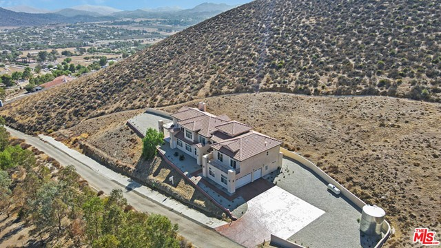 Gorgeous Contemporary Custom Mansion in Highly Sought-After Agua Dulce.  No expense was spared in the building of this 5,794 Sq Ft Beautifully Designed 5 BDR, 5BTH Home.  Built in 2007, this Private Lot has Spectacular Views! Whether you are looking for a High-End Weekend Retreat or Full Time Luxury Home this is the place to Enjoy Beautiful Sunsets from Multiple Balconies. Step inside to Large Foyer w/Travertine Tile, Hardwood Floors, Vaulted Ceilings, Crown Molding, Wrought Iron Spiral Stair-Case.  The Large Master Suite is one of a kind including Double Glass Doors & its own, Living room (w/possible Billiards/Library/Sitting Area), Office, Laundry, 2 Showers, Jacuzzi, Vanity, Walk in Closet.  Additional Jr. Master suite plus 2 more Bdr w/Jacknjill up. One more Master Suite located downstairs w/large closet, full bath, jacuzzi tub.  Large Formal Living & Formal Dininghas Fireplace & Double Doors leading to Outdoor sitting area w/Overhang.  Kitchen includes Hardwood Cabinets, Viking Refrigerator, Granite counters, Large Pantry, Separate Island w/Sink, Wetbar area.   Stamped Concrete Walkway, 3 Car Garage w/Additional Laundry Hookups, Large parking area with room for RV, 4 vehicles or more!! Zoned for horses with miles of trails nearby.  Seller motivated, make offer!!  Buyer to verify with appropriate entities all information.
