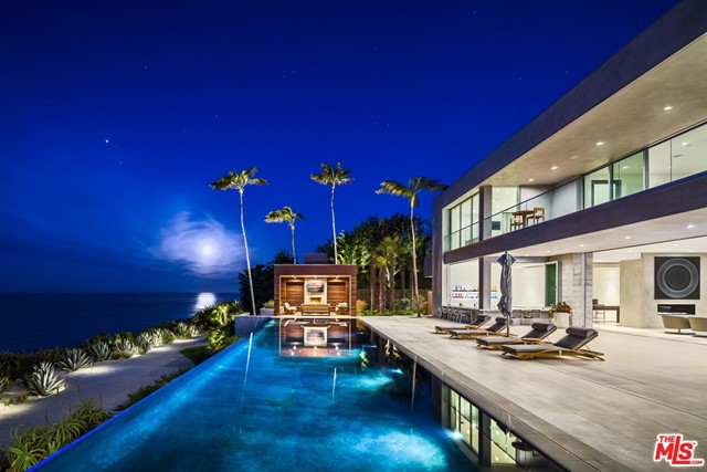 The Marisol Modern Estate is a true one-of-a-kind Malibu icon. This Doug Burdge-designed estate won multiple awards from the PCBC, the nation's most prestigious builder's conference, making it one of the most extraordinary homes in Southern California. This 7bd, 11ba, 9,793 sqft home will appeal to the most discerning buyers. It combines the feel of the world's finest luxury resorts with the most peaceful oceanside living Malibu has to offer right at your fingertips. This stylish yet very comfortable home is truly an owner's personal tranquil paradise confined within the privacy of its beautiful gates and only 25 minutes from the Camarillo Airport. The dramatic entrance is flanked by tropical landscaping and art that reveals wide walls of glass opening out to an infinity pool and the dramatic Pacific Ocean / coastal views. This jaw-dropping home includes a 67' infinity-edge pool flanked by two bungalows w/ fireplaces, an outdoor BBQ, a roof-top putting green, outdoor cabanas, an elevator, chef's kitchen, prep kitchen, movie theater, gym, sun decks, a saltwater coral aquarium, 5 car garage, gated security, indoor/outdoor bar, billiards room, and for the most discerning owners, a panic room. It is the perfect place to entertain, disappear into your own private enclave with all the amenities you may desire, and when you own this property you have arrived.