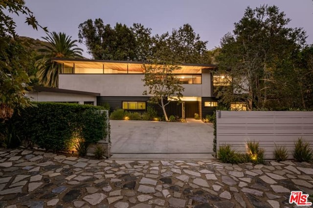 This Mandeville Canyon study of modernism represents the collaboration between its owners and architect Jesse Bornstein, AIA. References to L. A. s great modernists like A. Quincy Jones flow throughout as Bornstein used the spectacular site and its tree-shrouded surrounds as inspiration for the custom gated compound. The sustainable property encompasses a 4 bedroom, 3.5 bath main house with an office, den, gym, and a guest house with bath, pool and spa amid an arrestingly tranquil xeriscape. Timeless and natural materials such as polished concrete, ribbons of black aluminum, gypsum plaster and a rich mix of woods like Walnut and California Redwood blend with all manner and form of glass -clear, tinted, clerestory and retractable sliding folding doors creating dramatic, expansive, highly livable space that seamlessly interacts with the natural landscape and light. The two-story floorplan opens at its center into a gorgeous, broad living room and dining space with 20-foot ceilings, granite double-sided fireplace and walls of glass opening to nature. A superb gourmet kitchen with center island unfolds into the family room. An office, guest suite, utility room and powder bath complete the first level. An open broad-lit wide stairwell leads to a mezzanine open to below and gorgeous vistas beyond as the second level continues to balance proportion, light and a visual relationship to nature. The spacious primary suite rests in its own wing with a fireplace, generous his/her closet, and set behind exotic Shoji glass movable panels, a Zen bath with double vanities, spa tub and shower. Adjoining the primary suite is a gym and private patio with verdant overlook. The opposite wing contains an open den plus two spacious guest bedrooms with full bath. A canvas of custom details enhances the entire living space  indirect recessed and modern lighting fixtures, Brazilian black granite, Pennsylvania flagstone, built-in speakers, shelving and seating, plus a security system, 6-zone H