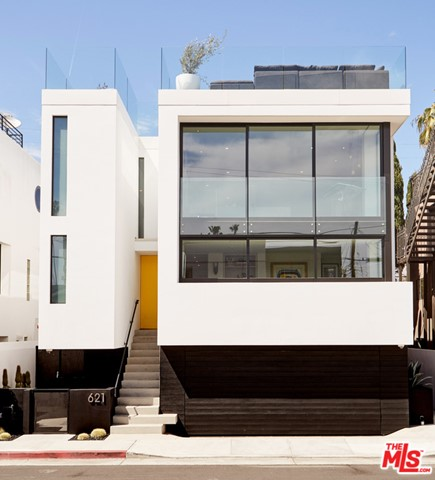 Home of L.A.-based rug designer Erik Lindstrom, this exquisite, contemporary Venice gem offers elegant seaside living amidst impeccable design, all with a focus on sustainable space planning. With three bedrooms, four baths and 2,766 square feet, enjoy city and ocean views and an ideal location. The facade makes an impression with soaring windows and an inviting yellow door. Inside, the great room offers a chic, open space to entertain, with a double-sided, metal fireplace. The Poliform kitchen beckons gourmet cooking with a burgundy marble backsplash set against gray cabinetry. The rooftop deck includes 360-degree city and ocean views and an expansive fire pit. The gorgeous guest suite opens up to a patio, lined with black bamboo. A two-car garage adds convenience and the prime location is moments away from canals, Abbot Kinney Boulevard, and the beach. Welcome to contemporary perfection, where aesthetics and pleasure preside.
