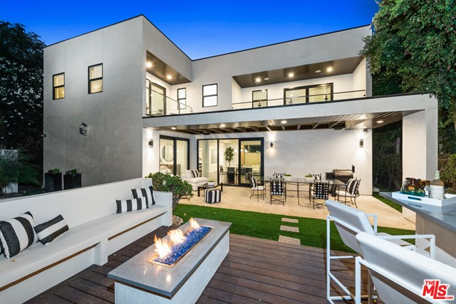 Located just moments from the heart of Beverly Hills, this 4 Bedroom 4 Bath gated contemporary home is set off the street to offer parking for up to 10 cars. Upon entering, one is welcomed with 10' high ceilings and an open concept living area. The chef's kitchen features sleek stainless steel appliances, Carrara marble countertops, and an oversized center island with a wine fridge. Flowing seamlessly into a spacious outdoor area, the backyard is equipped with a full outdoor kitchen, patio, fire pit, a tranquil waterfall feature, and an oversized spa for the ultimate entertainment experiences. The primary suite features a sitting area, a balcony overlooking the backyard, and a large walk-in closet. Generous Secondary Bedrooms are all en-suite. From the smart thermostat to the 70 framed-in flat screen, surround speakers, perimeter security cameras, 2017 Benedict Canyon Road offers an entertainment experience that can be enjoyed by all.