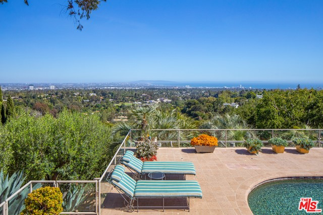 On a secluded 2.2+ acre knoll, with breathtaking views from downtown L.A. to the Pacific Ocean, this dazzling TWO RESIDENCE (two parcels) compound designed and later renovated by renowned architect, Richard Martin AIA, is a seamless blend of cutting-edge contemporary style, warmth, comfort and wrapped in an elegant traditional sensibility. Here is a unique and private world of uncommon quality and incomparable beauty.The MAIN HOUSE of approximately 7,500+ square feet encompasses 5 en-suite bedrooms, including a stunning primary bedroom with dual baths and walk-in closets, private view-oriented office, dramatic center island kitchen/family room, wine room, lower level screening room, game room and secure safe room/bomb shelter.  In addition, there is a separate professional gymnasium building with bath and private access. Bleached, wide plank hardwood floors, vaulted sky-lit ceilings, 3 fireplaces and two lavish outdoor patios blend harmoniously to create a rare and inviting lifestyle.Completely hidden from the main residence, and protected by a proscenium of lush garden landscape is a SECOND RESIDENCE (Guest House) of approximately 4,900+ square feet, also exquisitely renovated and updated by the current owner with the architect.  This luxurious residence has 3 generous bedrooms, 4 baths, double powder rooms, an elegant library/office, kitchen/family room, stunning formal dining room, 4 fireplaces and a completely private guest apartment with living room, bedroom, bath and kitchen -- all punctuated with hardwood floors, high ceilings, French doors throughout and city, ocean and mountain views. And the grounds ... reminiscent of the gardens of Tuscany and Provence, uniquely designed by landscape architect Nancy Goslee Power -- a profusion of color, specimen olive, palm and stately oaks, rolling lawns, gentle water elements, towering cypress, swimmers pool and carefully sculpted stone romantic pathways. Double large motor courts and covered parking for six cars comple
