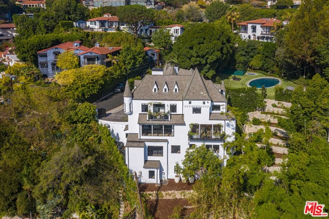 A castle-like Chateau in the hills above the Sunset Strip with panoramic views overlooking the city. Set behind private gates, this 7,732-square-foot smart home boasts 4 bedrooms and 7 bathrooms. A landmark estate on over 18,000 square feet, it offers countless amenities including a large backyard with a grass-edge saltwater pool and spa, terraced gardens with century-old trees, basketball court, outdoor pizza oven, screening room, music studio, a combination living and dining room that flows into a spacious Boffi kitchen with a Carrara marble island, Schotten & Hansen hardwood floors, and much more. Truly magical and unlike anything else on the market.