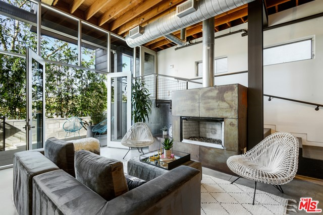 "This dramatic urban ""canal loft"" home (only one and a half blocks to the beach and adjacent to Venice canals) offers designer finishes and quality craftsmanship throughout. A private deck entry hidden by a wall of bamboo opens to the living-dining great room that features a distinctive fireplace. Impressive 14 ft. ceilings and steel-framed windows and doors distinguish the home's architectural uniqueness which merges reclaimed wood, walls of glass, and polished concrete floors. A gourmet kitchen features Viking and Sub-Zero stainless appliances, Caesarstone counters and breakfast bar. A floating stairway leads to upper levels where the loft can serve as office or den. A cozy master suite features a wall of reclaimed wood, generous walk-in closet and master bath with rain-waterfall shower. Abundant natural sunlight. The spacious rooftop deck offers city lights, mountain, canal and peek-a-boo ocean views perfect for entertaining friends and family. Private two-car garage + guest parking."