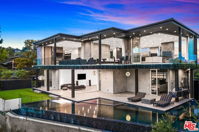 Perched at the end of a quiet cul-de-sac stands this custom modern trophy estate. Stunning views of DTLA, the coastline, and Crestwood Hills from every angle, as if you are floating on air. Designed around the art of entertaining, floor to ceiling glass panels seamlessly disappear & integrate the view, the outdoors, the wrap around deck and the interior space. This private oasis is truly a must see in person to experience the energy and privacy. A modern floor plan that features a large sleek fully equipped chefs kitchen, an oversized dining room & an enormous living room that overlooks the captivating views. The main suite rivals any 5-star hotel, with an oversized walk-in closet & spa like bathroom. The lower level consists of a gym, family room, glass wine room, & movie theater. Featuring 5 en-suite bedrooms and 8 baths laid out over 7,040 SF, a dramatic infinity pool, grassy pad and tons of space to bask in the sun and enjoy the So Cal weather. The ultimate modern view home.