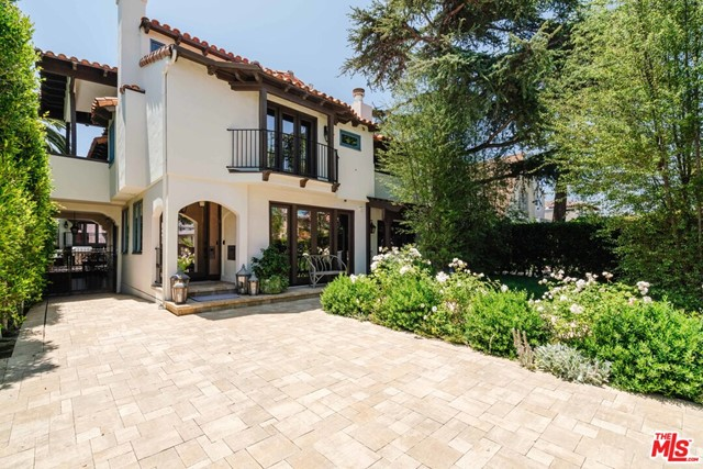 Set in the coveted North of Montana neighborhood, this 1924 Spanish revival compound has been meticulously updated with no expense spared. Through a gated and private entry, guests are welcomed into the elegant living room with fireplace flowing to a chef's kitchen with island, double Wolf range, Sub-Zero fridge, a cozy family/media room with dry bar, and guest suite with private terrace. Up the architectural stairway are 2 guest suites with a large patio, laundry, and the lux primary suite with 20ft ceilings, walk-in closets, impressive bathroom with shower and tub, and covered patios. The primary suite uses one of the guest rooms as an office/nursery/sitting area and is easily converted back to the 3rd upstairs bedroom. A large patio with BBQ flows into the backyard and the structure at the back of the property featuring a 4-car garage with original restored barn doors to the alleyway, and upstairs, an unparalleled guest house with an office, two fireplaces, wet bar, original restored wide plank flooring, vaulted ceilings, living room, bedroom, bathroom, and covered patio. Lutron and surveillance systems, 7 fireplaces, off-street parking for up to 8 cars, and top custom fixtures and finishes. Only a few doors up from the Montana Avenues boutiques, bars, coffee shops, and restaurants, this unprecedented offering is not to be missed. Main house sq. feet is approx 4,597 and the guest house sq. feet is approx 909 (see floorplan in attached docs section).