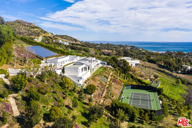 MOTIVATED SELLER! REMARKABLE VALUE FOR INCREDIBLE, OCEAN VIEW MALIBU COMPOUND WITH MAXIMUM PRIVACY. Years of dedication and passion, the home was built by & for the current owner focused on the awe-inspiring ocean views and features endless amenities which make you feel as-if you are at your own personal resort. The main level welcomes you with an open floorplan accented by fireplaces, built-ins & skylights flooding the space with natural light. Coastal living at its finest, floor-to-ceiling sliding glass doors are a staple allowing for indoor/outdoor flow to your outdoor oasis. Tucked in a private wing, sumptuous master with office, oversized windows, balcony & gorgeous marble bath. Grounds afford the residences with endless outdoor living with tennis court, pool, outdoor kitchen, & fruit orchards. Features solar panels, gourmet kitchen, well-appointed guest beds, staff quarters, theater, gym & laundry. Only moments from the best beaches, PCH, Malibu Country Mart & more.
