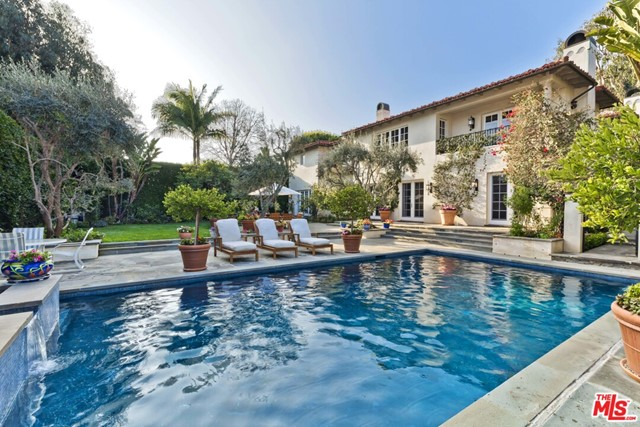 Reminiscent of a chateau in the South of France, this magical 5-bed, 6-bath, 6,725-SF Huntington Palisades residence is set on a generous 14,350-SF corner lot. Upon entry, guests are captivated by the stylish architecture, easy flow, and natural beauty of the spacious rooms. The dramatic living room with a beamed ceiling features a stone fireplace and French doors leading to a secluded patio with a firepit. Venetian plaster graces the formal dining room, butlers pantry, china pantry, and powder room. The chefs kitchen with Carrara marble countertops, large center island and walk-in pantry opens to the family room with a beamed ceiling and fireplace. The privacy-hedged, grassy yard features a pool, spa, large patios, dining area and outdoor kitchen with Wolf BBQ. The exquisite master boasts a sitting room, fireplace, balcony, huge walk-in closet, spa tub and steam shower. Four ensuite bedrooms, library/office, upstairs laundry room and 3-car garage complete this world-class offering.