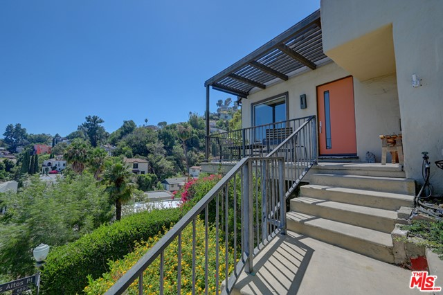 """Let Go of all the """"noise"""" in this beautiful  Private hideaway Residence in the Hollywood Heights , home to the famous High Tower next to the Hollywood Bowl & the Mann's Chinese theatre.  One must love stairs to appreciate living in this 2 bedroom, den, 2 baths  recently remodeled Contemporary Home. Open floor plan, Chef's gourmet kitchen, modern baths, high ceilings, central air/heat, wood floors, laundry rm.  Unique property offers 2 private garages  below the stairs on the street, well designed for parking & storage. Ready to move in and enjoy the spectacular views practically from every room plus the gorgeous front porch/balcony.  Rich with Hollywood stories by famous people who lived in the area, there are no power lines obstructing the stunning Views reminiscent of Hills in Italy, roof tiles like in Tuscany. ideal for seeking an active lifestyle taking advantage of the """"secret flight of stairs"""",  USPS & Amazon deliver direct to your door."""
