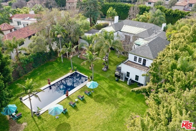 JUST REDUCED!!! An unparalleled property and personal residence of the late famed French Fashion designer, Christian Audigier. This palatial estate designed by noted architect, Gene Verge is perfectly situated on a sprawling corner lot in the heart of Hancock Park. Upon entering the gates of this near acre property you are transported you to your own private resort-style sanctuary unlike any other. Tastefully blending the elegance of a 1920's villa and 'Old Hollywood' sophistication w/the comforts of modern living. A dramatic foyer leads you to grand scale entertaining rooms on the main level that flows effortlessly outdoors. The 2nd sty provides a tremendous master suite w/a spacious private balcony, opulent en-suite bath & dual walk-in closets as well as 5 additional bedroom suites. The extraordinary outdoor living space includes a dining terrace fit for royalty, expansive rolling green lawn & a sparkling azure tiled swimmers pool, perfect for entertaining the most substantial of parties.